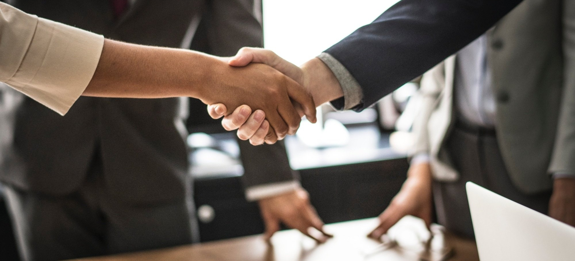 Human Resource shakes hand after onboarding new employee with documentation approved